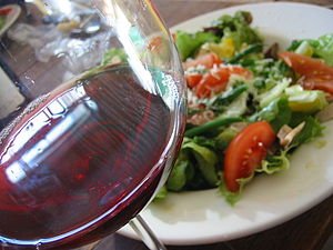 A glass of Beaujolais red wine with salad as b...