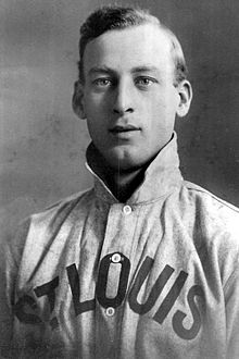 "A man wearing a baseball jersey with a raised collar and ""St. Louis"" written across the chest."