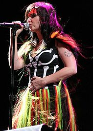 Colorful singer with long, dark hair onstage