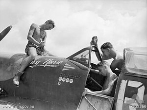 Two men sitting in and beside the cockpit, and another sitting astride the nose, of a military aircraft