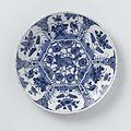 Bord van blauw en wit Delfts aardewerk, versierd met planten en vogels en een grommende wolf of vos in het midden.jpeg