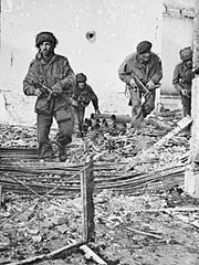 Four men in a bombed and gunshot building, walking towards the camera over rubble