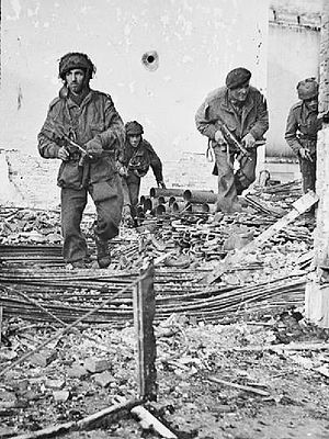 156th Parachute Battalion (United Kingdom) - Four men of the 156th Parachute Battalion moving through a shell-damaged house in Oosterbeek September 1944.