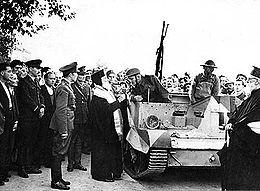 Un pope aux côtés d'une chenillette, sous les yeux de nombreux hommes, dont des soldats.