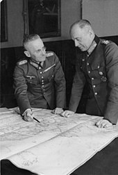 Photograph of Franz Halder looking at Walther von Brauchitsch who is standing to Halder's left as they study a map