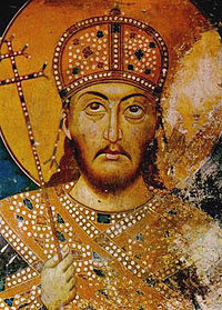 Upper torso and head of a middle-aged bearded man. He wears a domed golden crown, gold-decorated dress and carries a sceptre in the form of a patriarchal cross.