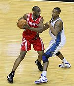 A basketball player, wearing a red jersey with the word «ROCKETS» in the front, is holding the basketball while another basketball player, wearing a white jersey, attempts to steal the ball.