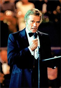Photograph of Charlton Heston in a suit addressing guests