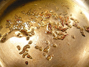 Tempering (spices) - Tempering (containing olive oil, fennel seeds, cumin seeds, fenugreek seeds, and slivered dried red chili peppers) being prepared in a saucepan