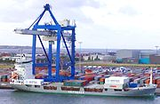 """Container ship """"Rita"""" being loaded at Copenhagen; note crew standing on deck, and stacks of containers on shore."""