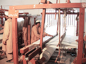 Bed sheet - Weavers work on a hospital bed sheet on a traditional manual loom in Faisalabad, Pakistan, in 2010