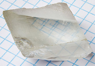 Birefringence - A calcite crystal laid upon a graph paper with blue lines showing the double refraction