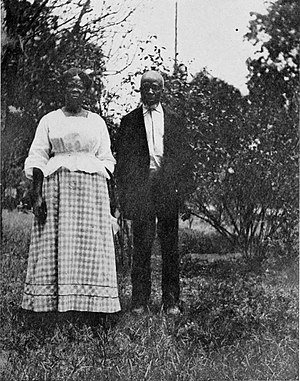 Cudjoe Lewis - Cudjo Kazoola Lewis photographed with Abache (Clara Turner) by Emma Roche, c. 1914. By then there were eight surviving members of the Clotilde group.