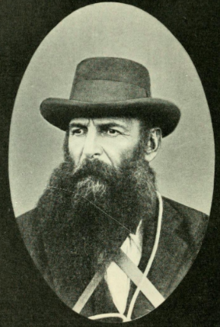 Black and white portrait of a middle-aged man with a beard and hat