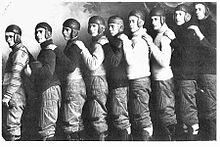 membros de uma equipe de futebol vestindo capacetes de couro à moda antiga