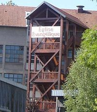 "Wooden three-story chalet on stilts, with a white sign on the top floor reading ""Église évangélique"""