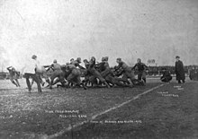 A grainy black and white photo of teams in sports jerseys and light padding contesting a play near the touchline, while watched by officials, coaches and crowds.