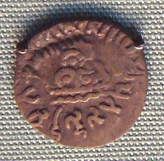 Overstrike (numismatics) - A coin of Nahapana overstruck by the Satavahana king Gautamiputra Satakarni. Nahapana's profile and coin legend are still clearly visible.