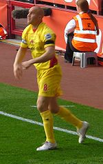 A man wearing a yellow football shirt and shorts, standing on the playing pitch.
