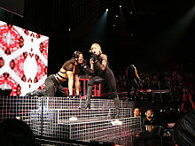 A blond woman sits on one leg on a stage while singing into a microphone in her right hand. With her left hand she approaches a man on all fours beside her. Both the man and the woman wear dark tight fitted costumes. Behind them, musical instruments lit in red light are visible.