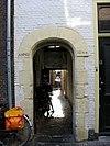 foto van Poortje met zandstenen omlijsting. Achteruitgang van Universiteitsbibliotheek die in 1593 naar Begijnhof overgebracht werd. Waarschijnlijk gebouwd als tweede ingang tot de Engelse Kerk die eveneens hier gevestigd was