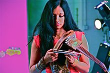 Gingger Shankar—an Indian woman in a black dress and black boots, with long black hair—plays 10-string violin onstage.