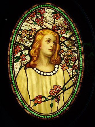 Tiffany glass - Girl with Cherry Blossoms illustrates many types of glass employed by Tiffany including elaborate polychrome painting of the face, drapery glass for the dress, opalescent glass for the blossoms, streaky glass in the border, fracture-streamer glass in the background and what may be iridescent glass in the beads.