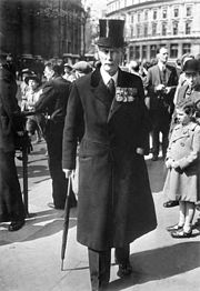a tall elderly man in formal attire and top hat walking on a city square