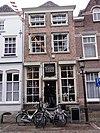 foto van Huis met schilddak en eenvoudige bruingeverfde lijstgevel, beneden winkel, met belangwekkend interieur met insteek