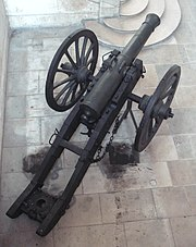 Top-view photo of a French cannon on a wheeled carriage. The top of the barrel includes a pair of handles