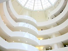 The plain white interior balconies spiraling around a rotunda under a huge skylight.