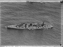 An aerial photograph of a large, World War I-era warship armed with four gun turrets, each with two guns, at sea. The ship is listing to port, but does not appear to be otherwise moving.