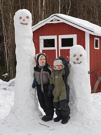 Ski suit - Children in snowsuits between two Hattifattener snowmen
