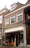 foto van Huis met eenvoudige laat 18e-eeuwse gevel, recht afgesloten, roeden in vensters op de verdieping. Winkelpui. Zadeldak met rode pannen. Zwarte pannen aan voorste schild
