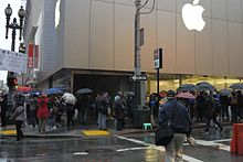 Customers standing in line in front of an Apple Store. The line is very long.