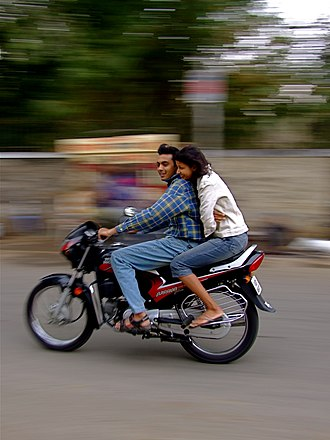 Motorcycling - A couple ride on a motorcycle in Udaipur, India
