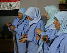Four young women in blue hijabs, holding brown belts