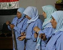 Neljä nuorta naista sinisillä hijabseilla, joilla on ruskeat vyöt