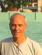 An upper-body photograph of a white man with balding grey hair, smiling at the camera while wearing a grey shirt.