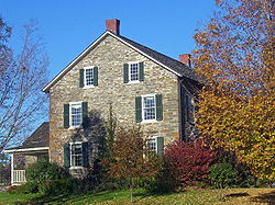 Side view of a stone house with pointed roof, two chimneys and a small wing on the left. On the right is a tree whose leaves are changing with autumn.
