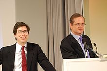 Zittrain smiling and Lessig speaking, both in suits