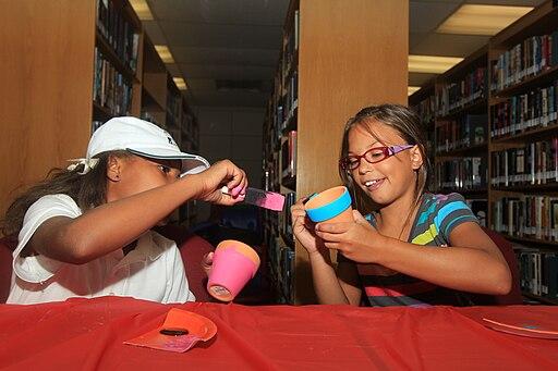 Kids painting flowerpots during the Summer Reading Program