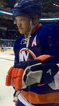 "Kyle Okposo wearing a blue home Islanders jersey with an assistant captain ""A"" on it, with a blue helmet on"