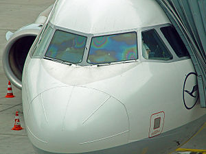 Indium tin oxide - Thin film interference caused by ITO defrosting coating on an Airbus cockpit window. The film thickness is intentionally non-uniform to provide even heating at different distances from the electrodes.