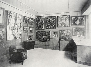 Section d'Or - La Section d'Or exhibition, 1925, Galerie Vavin-Raspail, Paris. Albert Gleizes' Portrait de Eugène Figuière, La Chasse (The Hunt), and Les Baigneuses (The Bathers) are seen towards the center. Works by Robert Delaunay and André Lhote are seen to the left and right respectively, amidst works by others