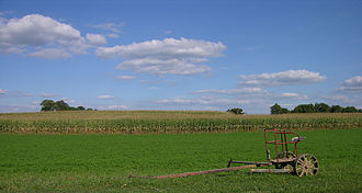 Lancaster County, Pennsylvania - A typical Lancaster County farm with a horse-drawn farm implement near a corn field