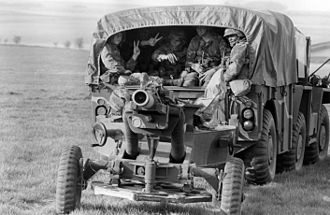 Allied Command Europe Mobile Force - U.S. soldiers wave from the back of a Gama Goat towing a howitzer from a drop zone during NATO Exercise Ardent Ground '87 on 24 April 1987.