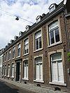 foto van Huis met brede lijstgevel, voorzien van hardstenen omramingen met gecanneleerde steentjes onder de zijkanten.