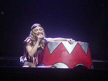 Image a blonde woman wearing red-and-white Circus outfits and using a black tiara. She is sat-down on the floor and is holding a michophone to her mouth, with her eyes closed.