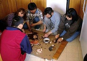 Muktuk - A group of people eating muktuk, 1997